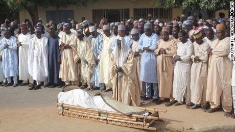 Men attend the burial prayer Thursday of a victim of an attack on the Borno State governor's convoy.