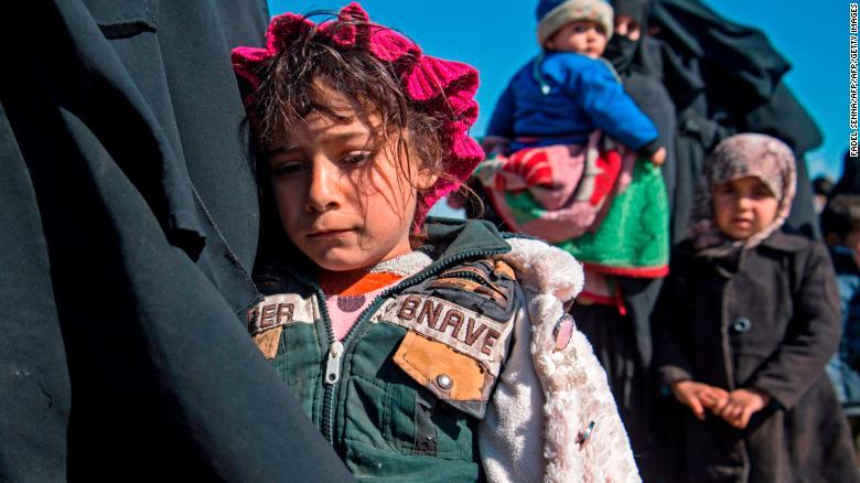 Женщины и дети стоят на поле после бегства из района Багхуз в восточной сирийской провинции Дейр-Эззор 12 февраля.