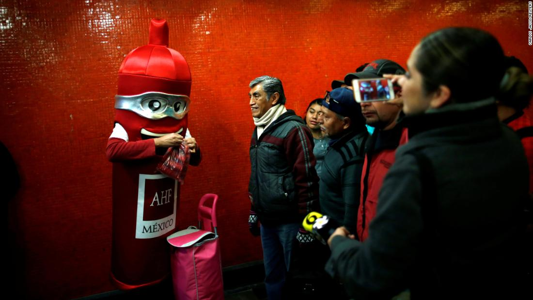 A man in a condom costume gives out free condoms at a metro station in Mexico City on Wednesday, February 13. It was International Condom Day.