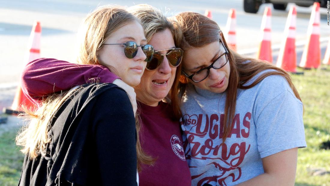Cheryl Rothenberg and daughters Emma and Sofia view a memorial on the one-year anniversary of the massacre at Marjory Stoneman Douglas High School in Parkland, Florida. Gunman Nikolas Cruz, a former student, slaughtered 17 people at the school on February 14, 2018.