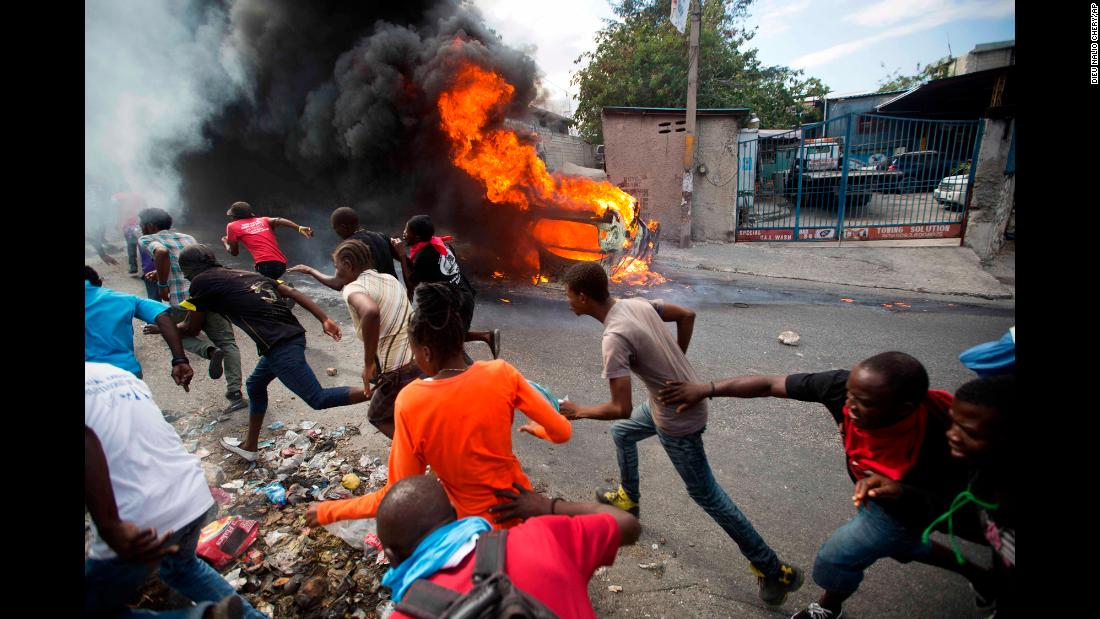 Protesters demanding the resignation of Haitian President Jovenel Moise run away from police shooting in their direction as a car burns nearby in Port-au-Prince, Haiti, on Tuesday, February 12.