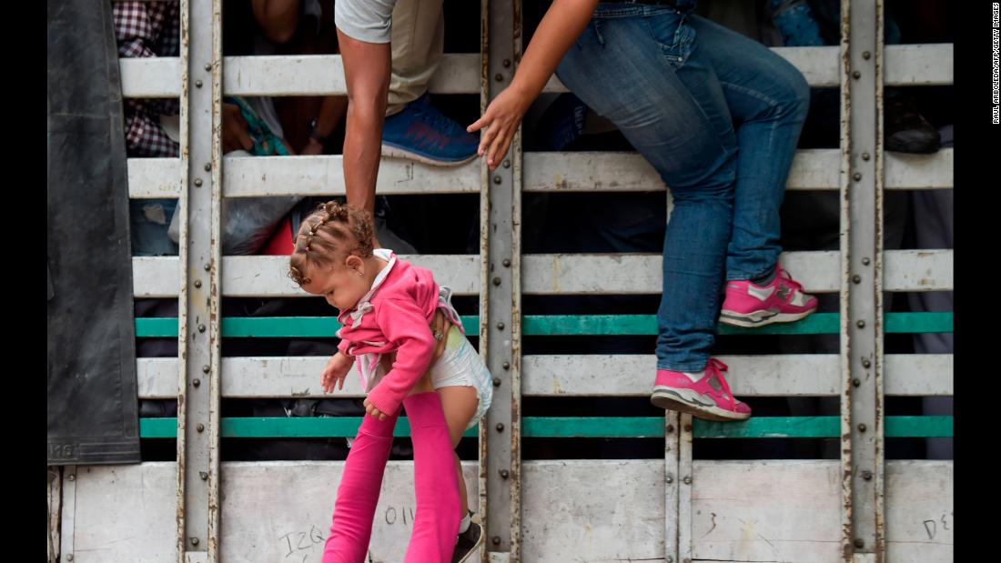 Venezuelan migrants climb on a truck as they travel in Colombia on Sunday, February 10.