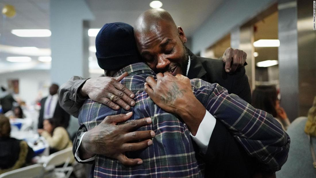 Gregory Harris, right, is hugged by supporters at the Los Angeles Mission after completing a one-year residential program on Friday, February 8. Harris is one of 12 students who were part of the Mission's 100th graduating class.