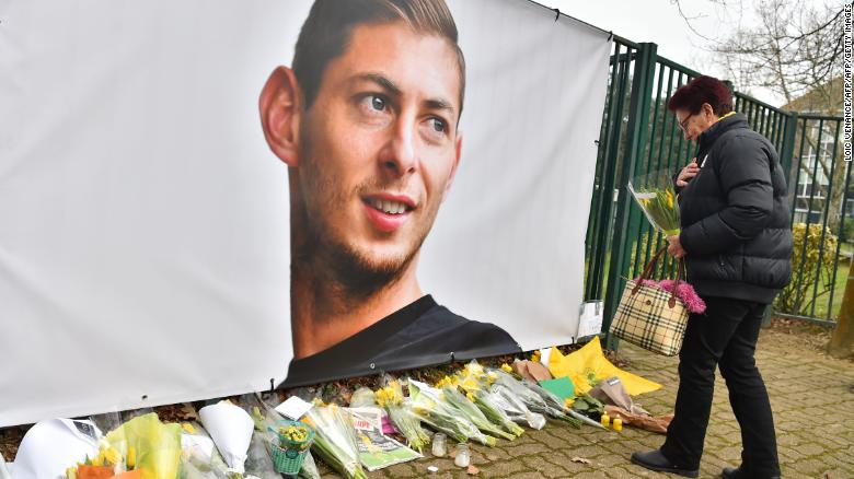 A woman lays flowers beside a portrait of Argentinian forward Emiliano Sala.