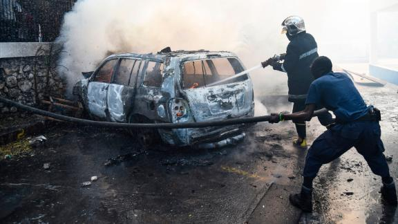A firefighter extinguishes a car fire at the offices of Television Nationale d'Haiti during protests in Port-au-Prince on Wednesday.