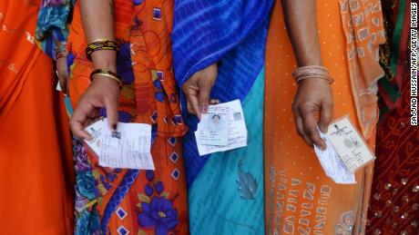 Indian voters pose with their voting slips as they stand in a line to cast their vote outside a polling station at Dabua village on the outskirts of Faridabad on April 10, 2014.