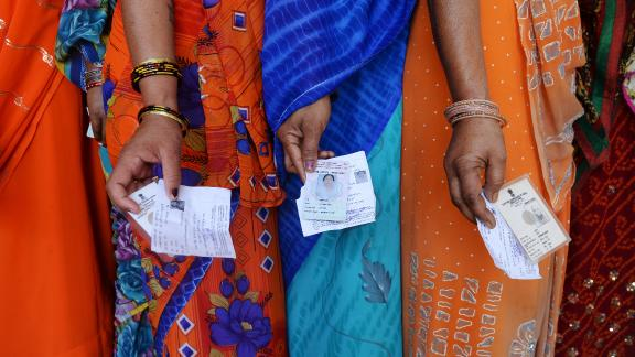 Indian voters pose with their voting slips as they stand in a line to cast their vote outside a polling station at Dabua village on the outskirts of Faridabad on April 10, 2014, during the third stage of voting for national elections in the northern state of Haryana. India
