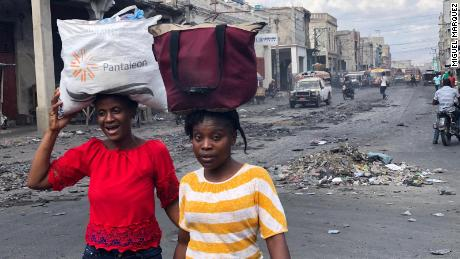 Two women walk Saturday in downtown Port-au-Prince , which is usually busy with shoppers.