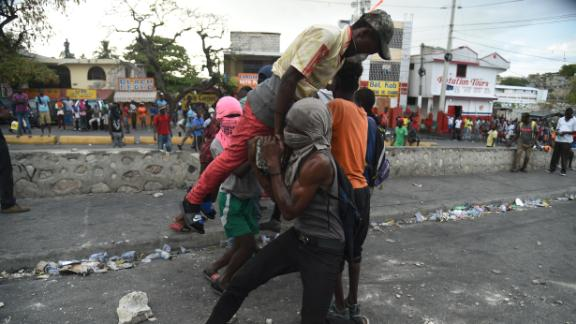 Demonstrators try to place a barricade during clashes with Haitian police in Port-au-Prince on February 15.