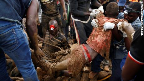 A rescued miner is carried from a pit at the mining site on Saturday.