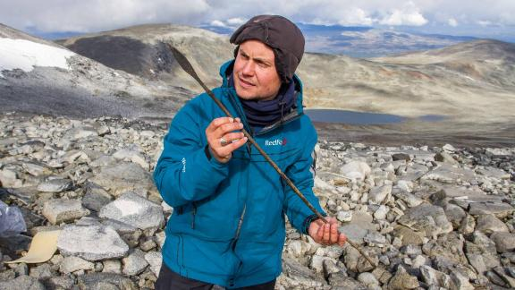 A member of the Secrets of the Ice team holds a completely preserved 1,400-year-old arrow, radiocarbon-dated to c. AD 600.