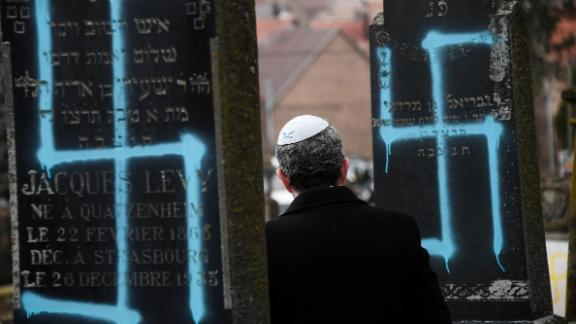 A man walks by graves vandalised with swastikas at the Jewish cemetery in Quatzenheim, on February 19, 2019, on the day of a nationwide marches against a rise in anti-Semitic attacks. - Around 80 graves have been vandalised at the Jewish cemetery in the village of Quatzenheim, close to the border with Germany in the Alsace region, which were discovered early February 19, 2019, according to a statement from the regional security office.