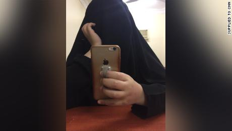 "The younger sister takes a selfie in a hotel room. They say they felt like ""ghosts"" under the full-length black robe, as if they were invisible, not there."
