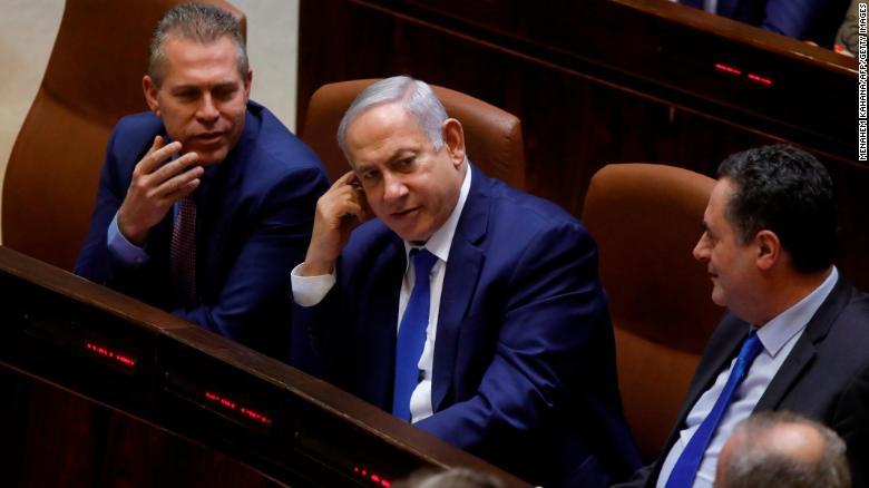 Israeli Prime Minister Benjamin Netanyahu sits among Likud party MPs Gilad Ardan (L) and Israel Katz (R).