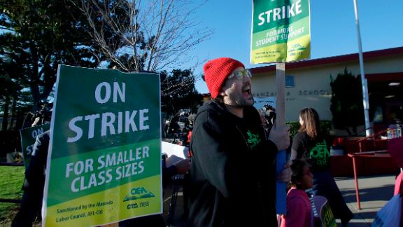 Garrick Ruiz, union member with United Teachers of Los Angeles, center, yells while teachers and supporters march outside of Manzanita Community School in Oakland, Calif., Thursday, Feb. 21, 2019. Teachers in Oakland went on strike Thursday in the country's latest walkout by educators over classroom conditions and pay. (AP Photo/Jeff Chiu)