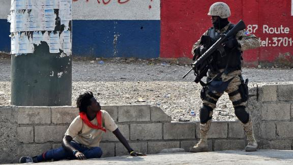 A police officer questions a man near the airport in Port-au-Prince on Friday, February 15.