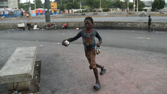 A boy flees from tear gas during clashes in Port-au-Prince on February 15.