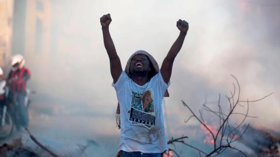 A demonstrator stands in the street chanting slogans against President Moise on February 9.