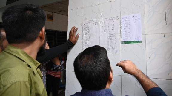 People search for their relatives' names on a list of people who were injured when a fire broke out in Dhaka.