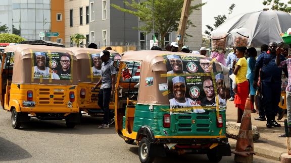 Rickshaws emblazoned with campaign posters bearing images of the opposition Peoples Democratic Party election candidate Atiku Abubakar and his running mate Peter Obi stand on a road in Abuja on February 19, 2019, ahead of rescheduled general elections.