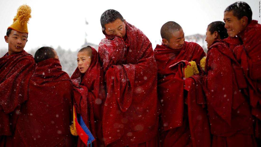 Tibetan monks attend a ceremony Sunday, February 17, during the Sunbathing Buddha Festival in China's Gannan Tibetan Autonomous Prefecture.