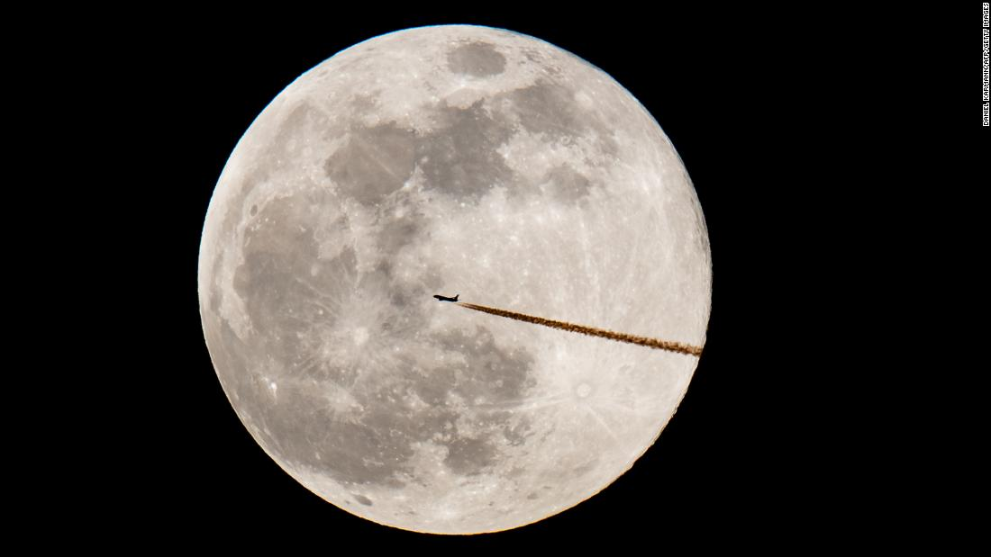 """A """"super snow moon"""" is seen behind a plane as it flies over Nuremberg, Germany, on Tuesday, February 19."""