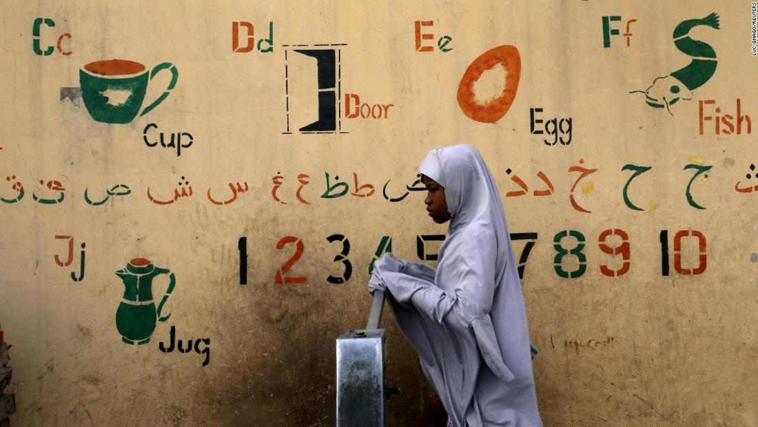 A girl draws water from a fountain in Kano, Nigeria, on Sunday, February 17, a day after the country's elections were abruptly postponed. Authorities, citing logistical issues, moved the vote to February 23.