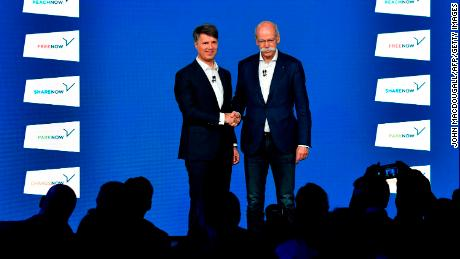 BMW CEO Harald Krueger shakes hands last week with Daimler CEO Dieter Zetsche.
