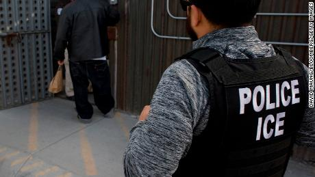 U.S. Immigration and Customs Enforcement (ICE) agents look on as an undocumented man is received by a Mexican immigration agent at a removal gate of the U.S.-Mexico border in San Diego, California, U.S., on Thursday, Feb. 26, 2015. The U.S. Department of Homeland Security is nearing a partial shutdown as the agency's funding is set to expire Friday -- something Senate Majority Leader Mitch McConnell had said wouldn't happen on his watch. Photographer: David Maung/Bloomberg via Getty Images