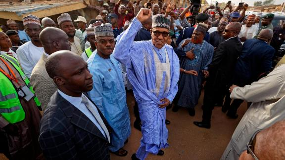 Nigeria's President, Muhammadu Buhari, gestures to supporters after casting his vote in his hometown of Daura.