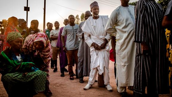 People line up to vote in the presidential election a few hours before polls open at Shagari Health Unit polling station in Yola.
