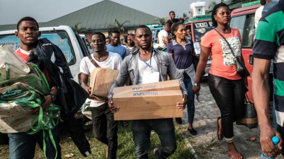 Electoral commission staff deliver items to a polling station in Port Harcourt after voting was due to begin.