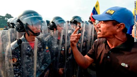Venezuelans confront national policemen demanding them to let the humanitarian aid in, at the Simon Bolivar bridge, in Cucuta, Colombia after President Nicolas Maduro's government ordered to temporary close down the border with Colombia on February 23, 2019. - Venezuela braced for a showdown between the military and regime opponents at the Colombian border on Saturday, when self-declared acting president Juan Guaido has vowed humanitarian aid would enter his country despite a blockade. (Photo by Luis ROBAYO / AFP)        (Photo credit should read LUIS ROBAYO/AFP/Getty Images)