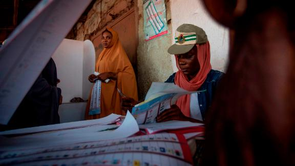 A polling station worker checks and counts ballot papers at Badarawa Junction polling station in Kaduna.