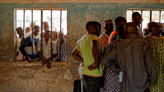 People peer through a window as party agents huddle together to watch votes being counted inside a polling station in Kano, Nigeria.