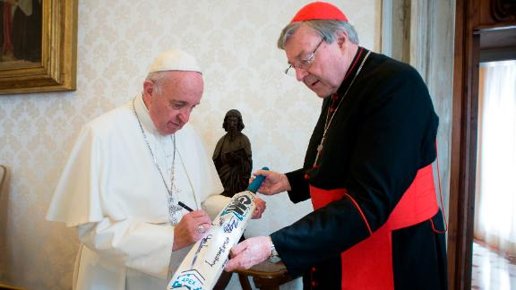 Pope Francis signs a cricket bat he received from Cardinal George Pell, at the Vatican on October 29, 2015.