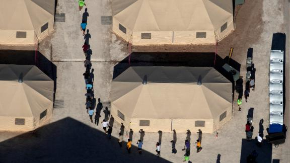 Immigrant children who had been separated from their families walk between tents at a temporary shelter in Tornillo, Texas, on June 18, 2018.