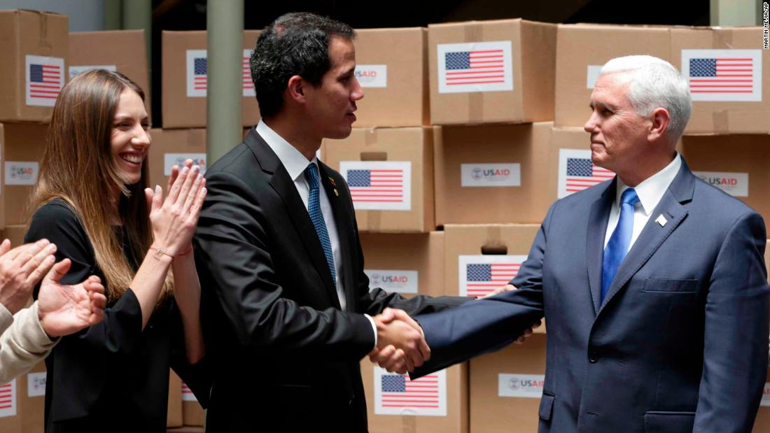 Guaido shakes hands with Pence in Bogota, Colombia, on Monday, February 25. The room was filled with humanitarian aid destined for Venezuela. Guaido's wife, Fabiana Rosales, is pictured at left.