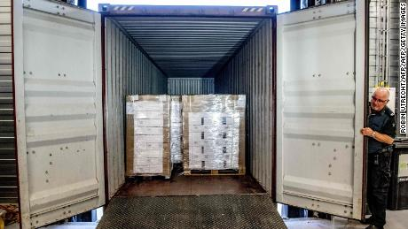 A customs official displays a container with 90,000 bottles of vodka after it was intercepted in the port of Rotterdam.