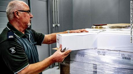 A customs official handles boxes inside a container of 90,000 bottles of vodka intercepted in the port of Rotterdam.