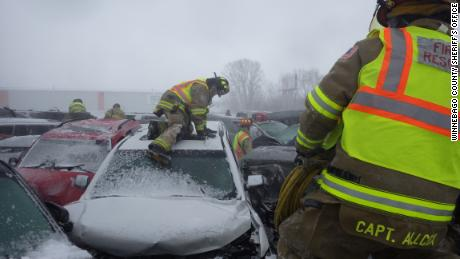 Firefighters climb over vehicles in Sunday's chain-reaction crashes.