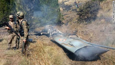 Pakistani soldiers stand next to what Pakistan said was the wreckage of a downed Indian fighter jet on February 27, 2019.