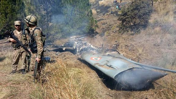 Pakistani soldiers stand next to what Pakistan says is the wreckage of a downed Indian fighter jet on February 27.