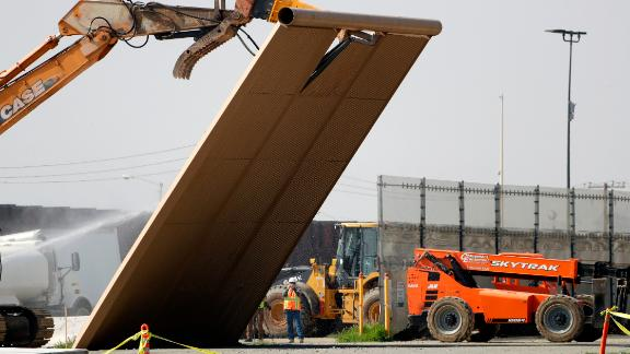 A border wall prototype falls during demolition at the border on Wednesday.
