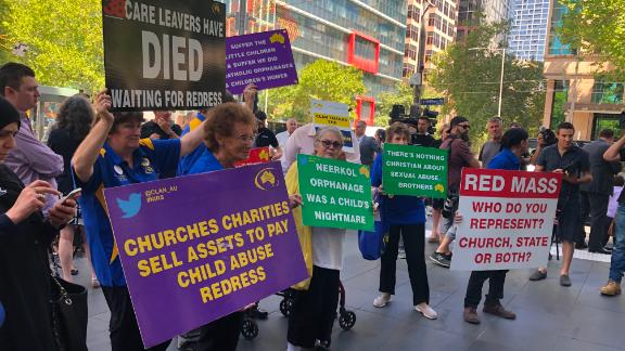 Protesters hold signs outside the County Court in Melbourne, Victoria on February 27, 2019 during a hearing for convicted pedophile Cardinal George Pell.