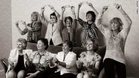 The Original Nine recreate their iconic photo from 1970 in 2012, with Julie Heldman (bottom right), who was not in the original image, replacing her mother. The women are holding one-dollar bills, which commemorate the symbolic professional contracts they signed in order to affirm their commitment to the Virginia Slims Circuit.