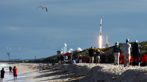 People watch from Playalinda Beach at Canaveral National Seashore as a SpaceX Falcon 9 rocket successfully launches carrying the Es