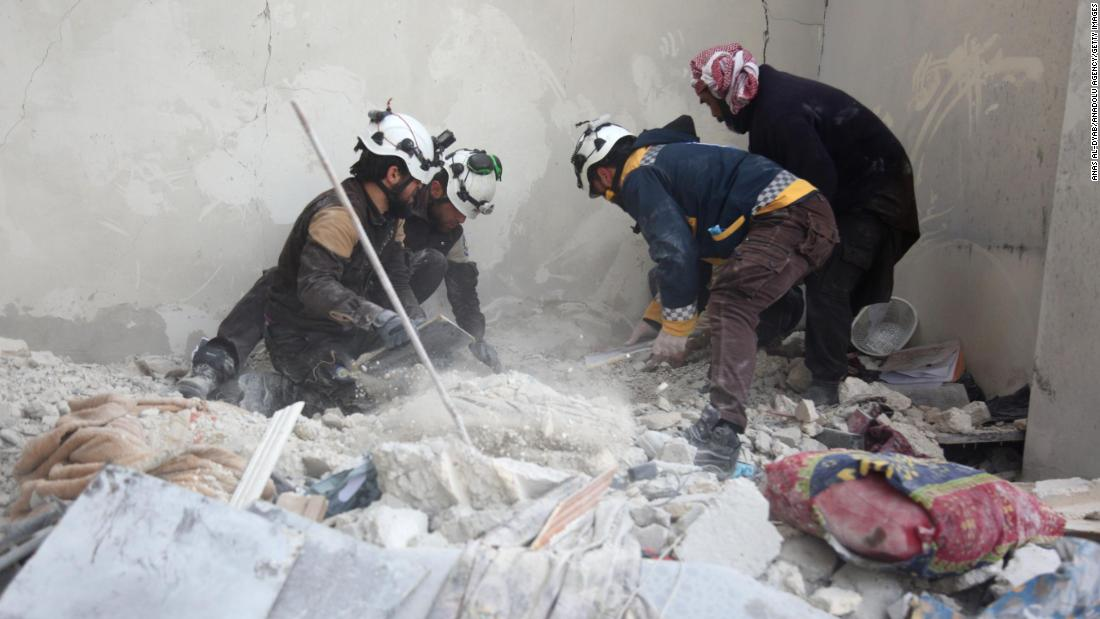 Members of the Syrian Civil Defense, a humanitarian group also known as the White Helmets, work at the site of the airstrike on Tuesday.