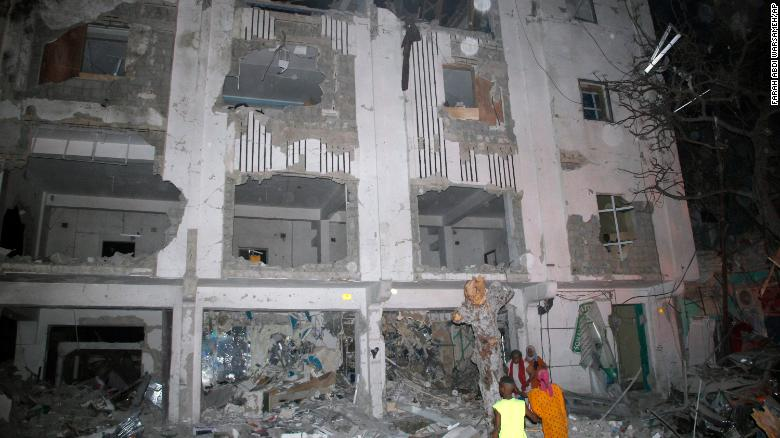 Somalis walk near a destroyed building after a car bomb in Mogadishu, Somalia, Thursday.