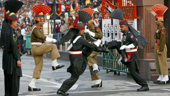 "TO GO WITH AFP STORY ""Pakistan-vote-India-peace"" by Charlie McDonald-Gibson In this picture taken on February 20, 2008 at the Wagah border post with India, some 30 km from Lahore, Pakistani honour guards (black uniforms) and Indian rangers (background) take part in the daily flag-lowering ceremony.  Every evening as dusk falls on the India-Pakistan border post near Lahore, crowds gather on either side of the frontier and scream slogans at each other in a choreographed show of bravado. India on February 20 welcomed the elections in Pakistan and said it hoped to see fresh talks with its nuclear-armed South Asian rival.           AFP PHOTO/LIU Jin (Photo credit should read LIU JIN/AFP/Getty Images)"